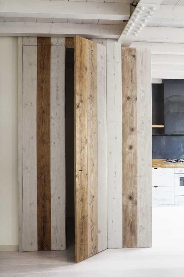 Дверь в шкаф из дерева разных оттенков подчеркивает натуральность материалов отделки кухни.