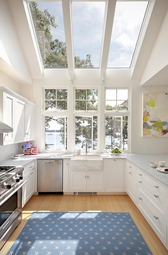 Современный белый дом на берегу озера. Остекленная крыша кухни дополняет окно с видом на озеро и добавляет ощущения связи с окружающей природой.