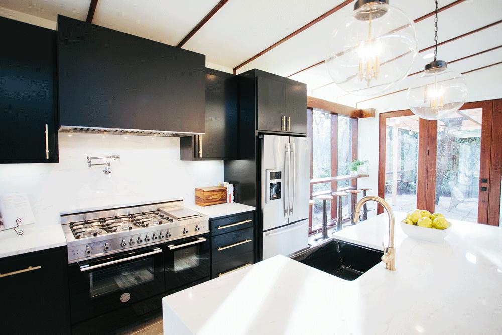 После реконструкции. Рабочая зона кухни с черной мебелью размещена вдоль задней стены дома.