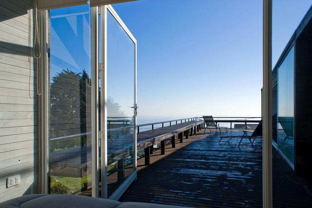 Мирокие остекленные окна-двери из главной спальни открывают роскошный вид на океан.