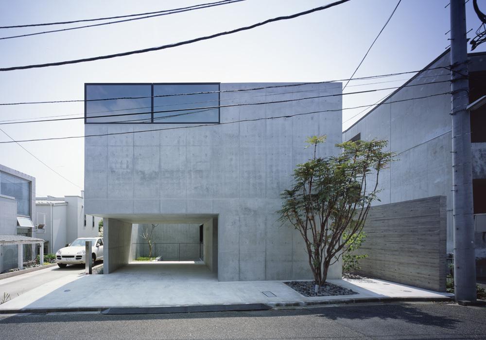 Фасад дома, на первом этаже крытая парковка на два автомобиля.