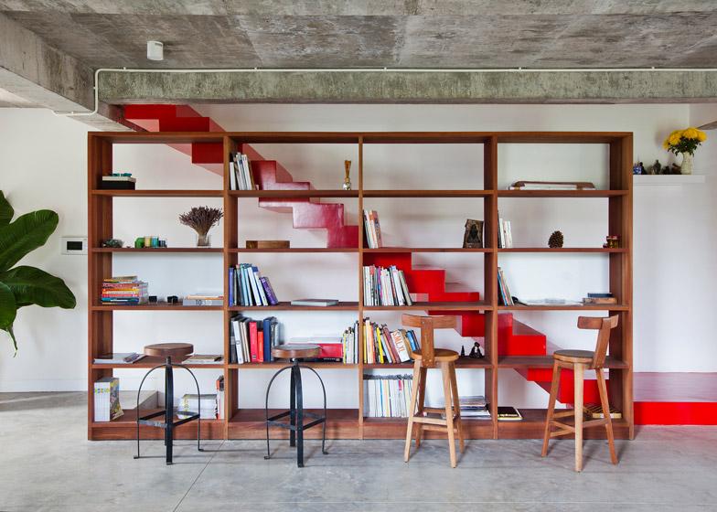 Лестница на мансарду проходит за книжным шкафом.
