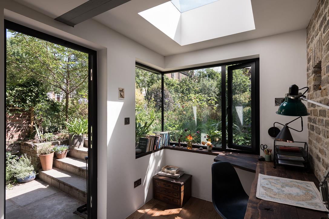 Из офиса в сад ведет широкая стеклянная дверь.